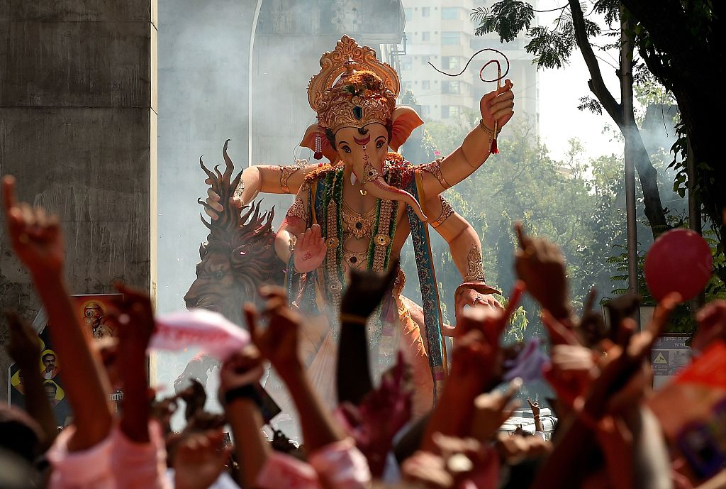 Indian Hindu devotees take part in a procession before the immersion of a huge idol of the elephant-headed Hindu God Lord Ganesha in Mumbai on September 27, 2015. During the eleven-day Ganesh Festival Hindu devotees bring home idols of Lord Ganesha and offer prayers in temporary temples in order to invoke his blessings for wisdom and prosperity, culminating with the immersion of the idols in bodies of water, including the ocean on the last day. AFP PHOTO/ PUNIT PARANJPE / AFP / PUNIT PARANJPE        (Photo credit should read PUNIT PARANJPE/AFP/Getty Images)